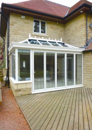 Ultraframe conservatory featuring bi-fold doors and structural eaves beam